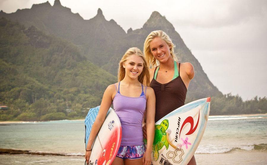 Bethany Hamilton and AnnaSophia Robb both holding surfboards on the beach.