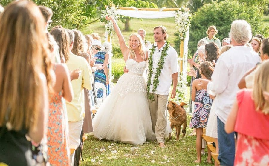 Bethany and her husband Adam walking down the aisle after their wedding ceremony, surrounded by friends and family.