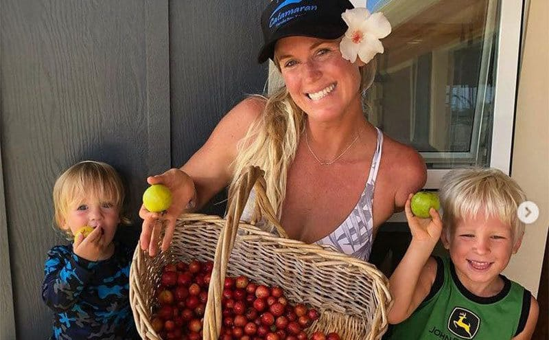 Bethany is sitting on a bench with her two boys, holding a very large basket of guava fruit.