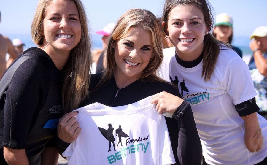 """Three young women posing for a photo with """"Friends of Bethany"""" T-shirts at an event on the beach."""