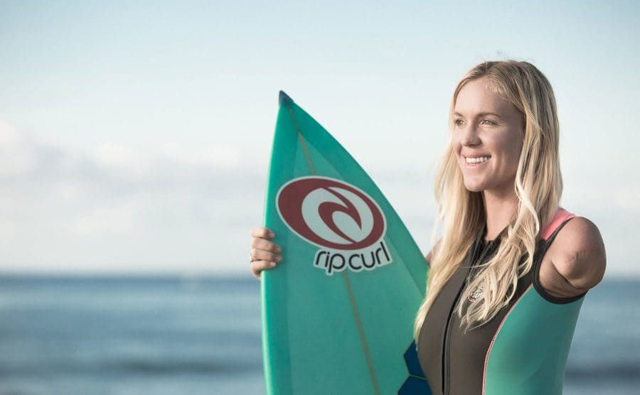 Bethany is holding a surfboard while posing for a photo.