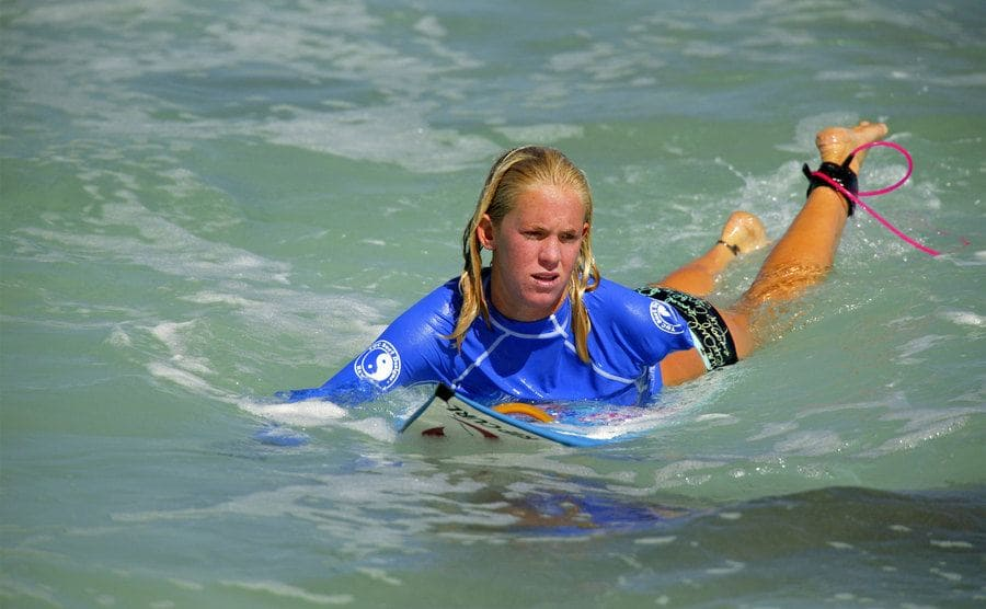 Shark attack survivor Bethany Hamilton paddles to shore after competing in Round 1 of the Town & Country Surf Women's Pipeline Championship.