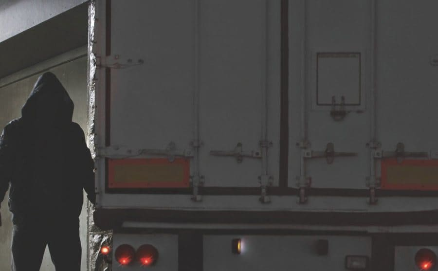 A hooded figure approaches and semi-truck in the cover of dark.