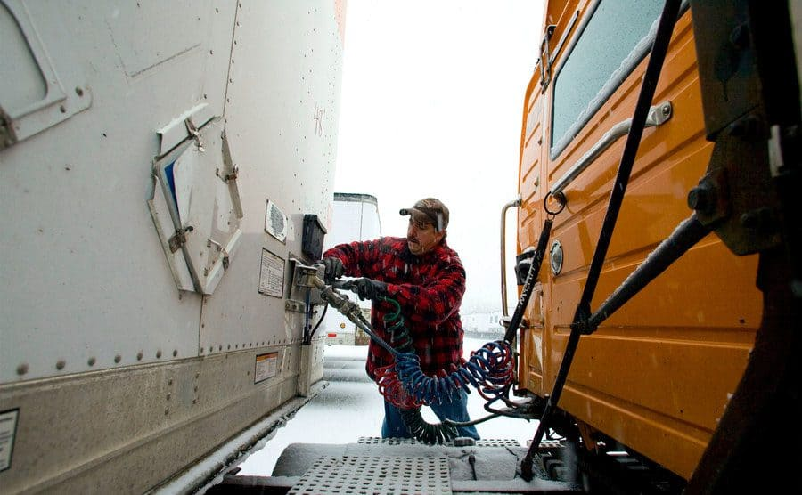 A man attaching the cables between the trailer and the cab.