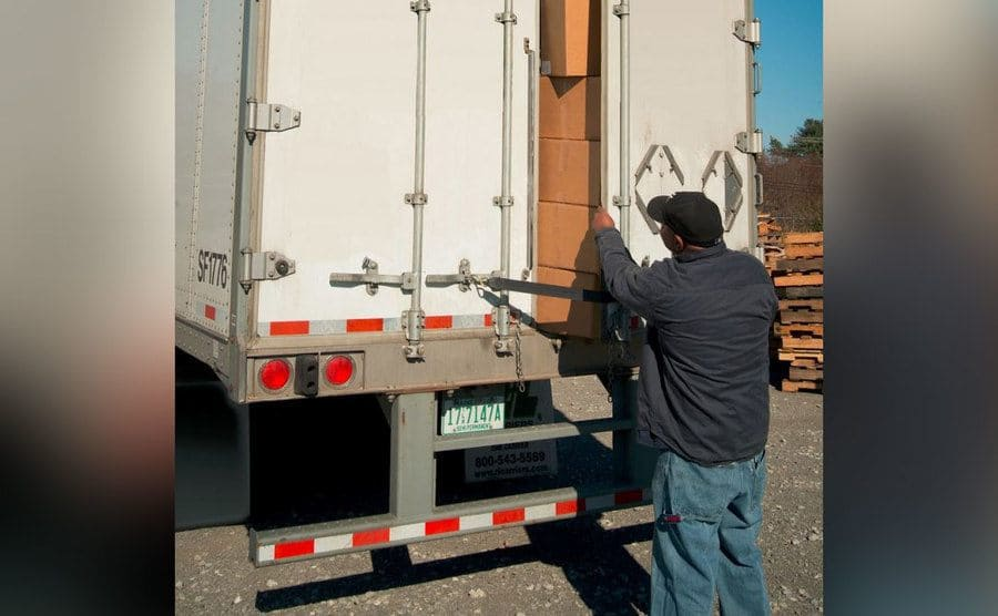 A man opening up the back of a semi, the truck is filled with boxes.