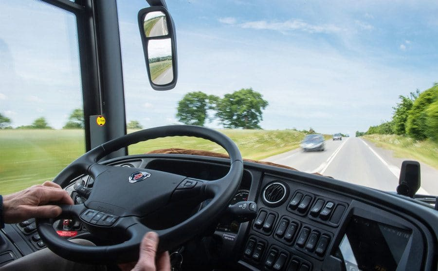 Front window view of the Highway and the dashboard, with the driver's hands on the wheel.