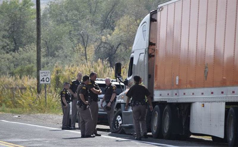 Highway patrolmen standing next to a semi after having chased the driver.