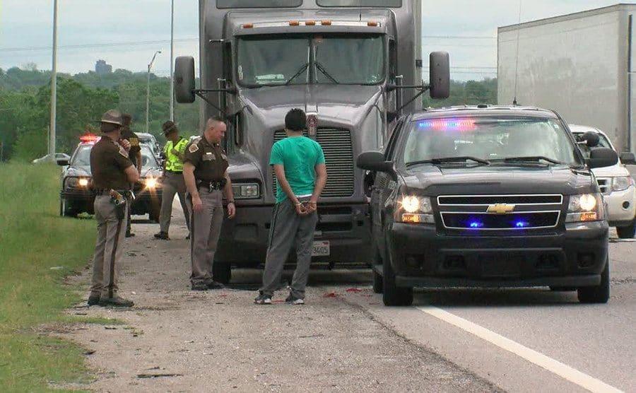 Patrolmen arrest a semi-truck driver on the side of the road.