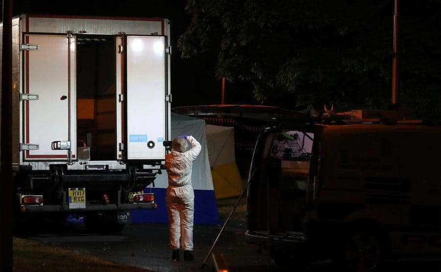 A forensic officer taking pictures of the back of a semi-truck.