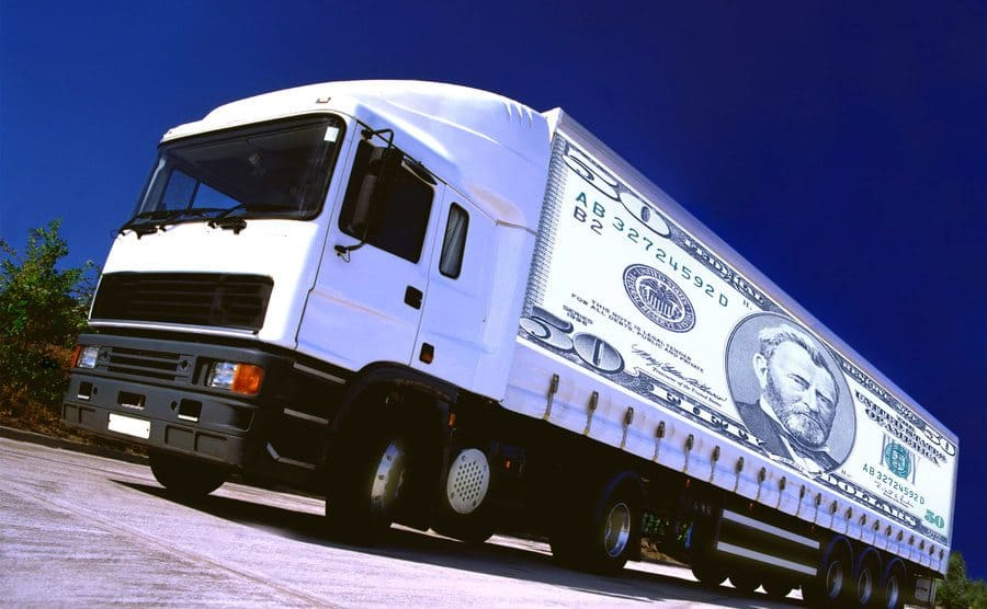 A sideview of a semi with a printed 50-dollar bill blown up on the side of it.
