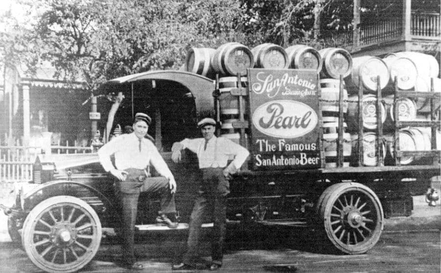 An old photo of two drivers standing next to their truck filled with beer.
