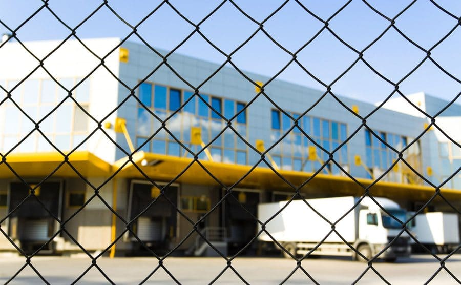 The loading dock of a distribution center through a metal fence with tucks loading up.