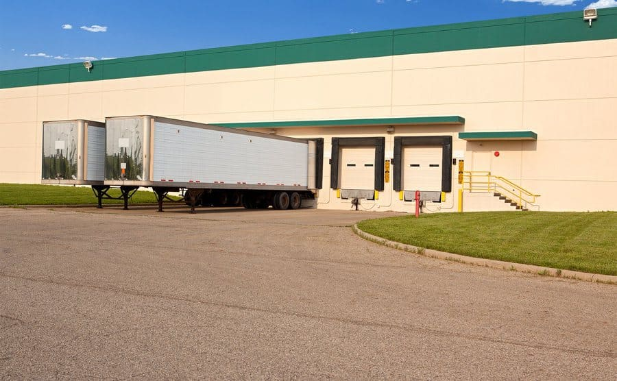 Two semi-truck trailers at a loading dock.