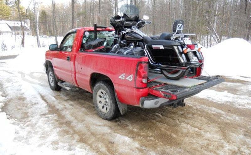 A Harley-Davidson Motorcycle on the back of a red pick up truck.