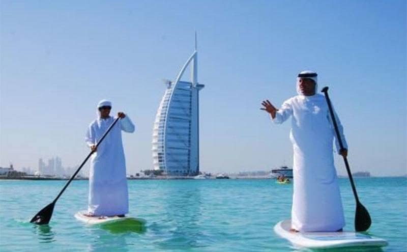 Two men on paddleboards standing up rowing in full dress