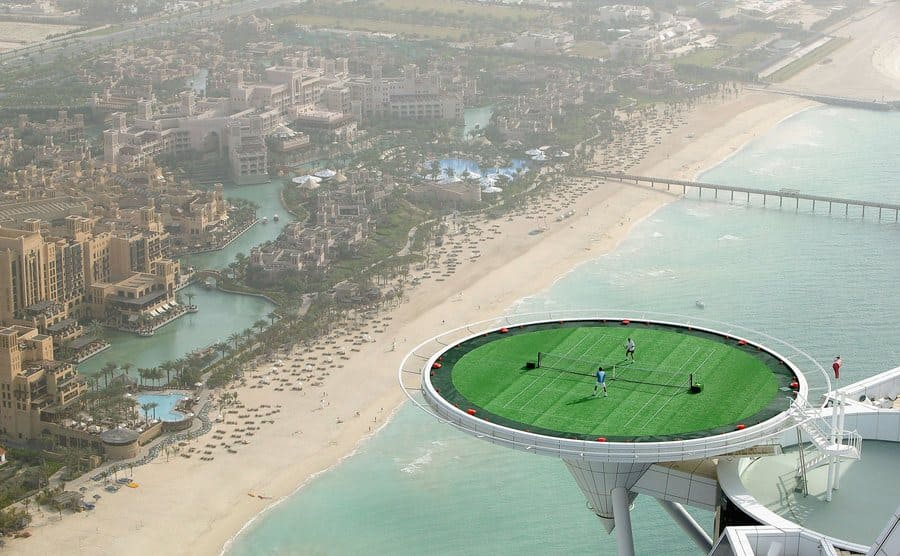 A large round tennis court sticking off the top of a skyscraper hotel