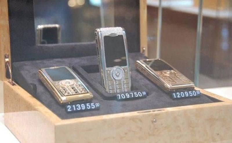 Three cell phones covered in diamonds on display in Dubai