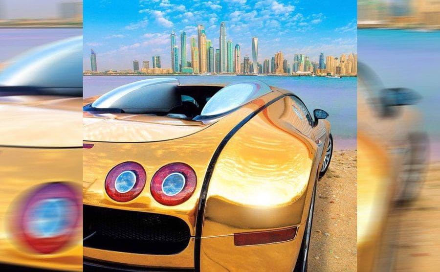 A gold sports car parked on the beach looking at a skyline across the water