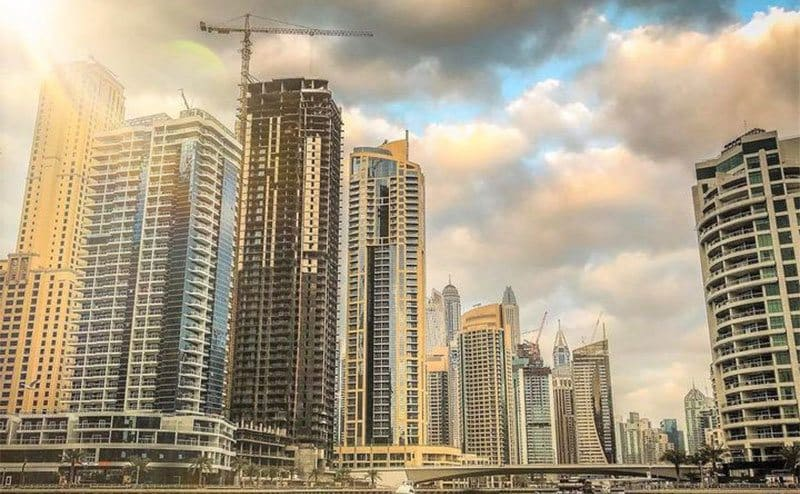 A skyline view of Dubai with the sun shining from in between clouds