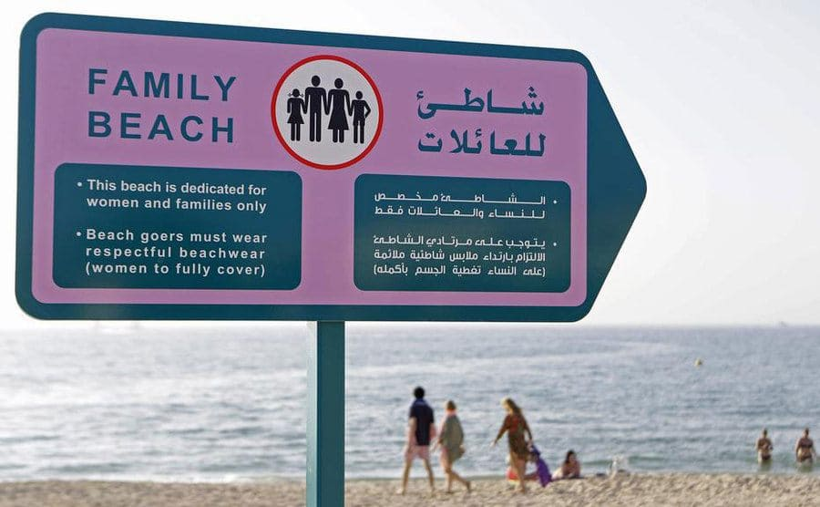 A sign for the beach mentioning that it is a family beach and men can only enter with family