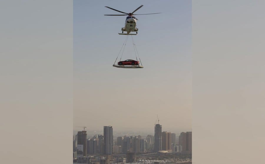 A car being transported underneath a helicopter