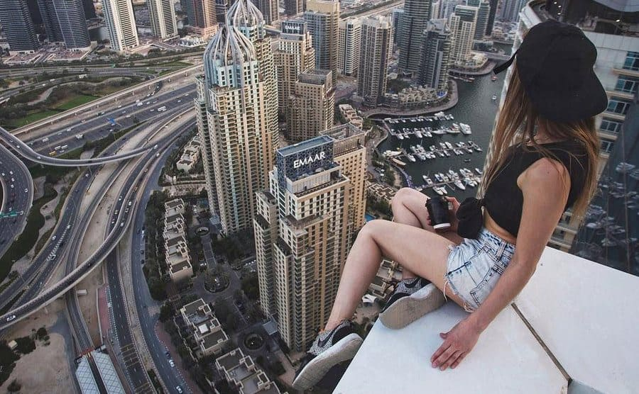 A girl sitting on the ledge of the roof of a tall building looking out over the skyline