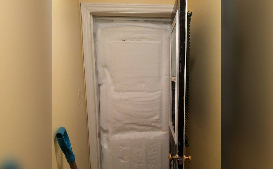 Snow piled up till the top of a door frame; you can see a small finger indent in the snow indicating that someone tried to push out.