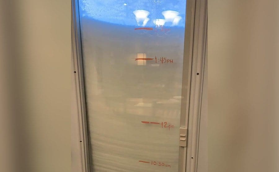 Snow piled up against a glass door with markings showing the snow's progressing levels rising by hours.