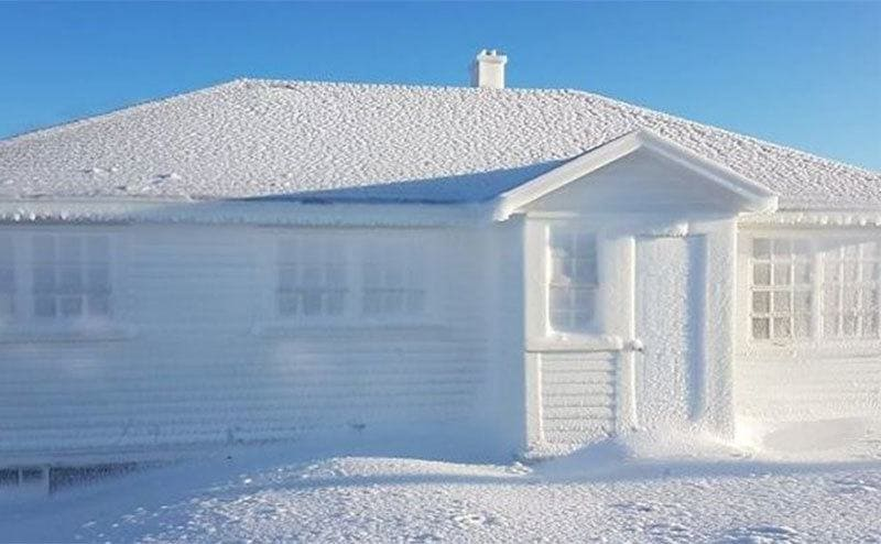 A home perfectly covered in snow, even the windows are frozen shut.