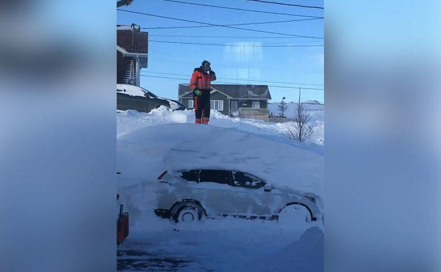 A man is talking on the phone as he stands on a mountain of snow that has his car buried underneath.