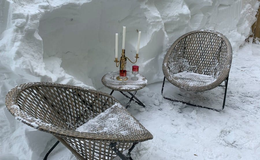 Candlesticks and wine glasses set up on outdoor furniture next to a wall of snow.