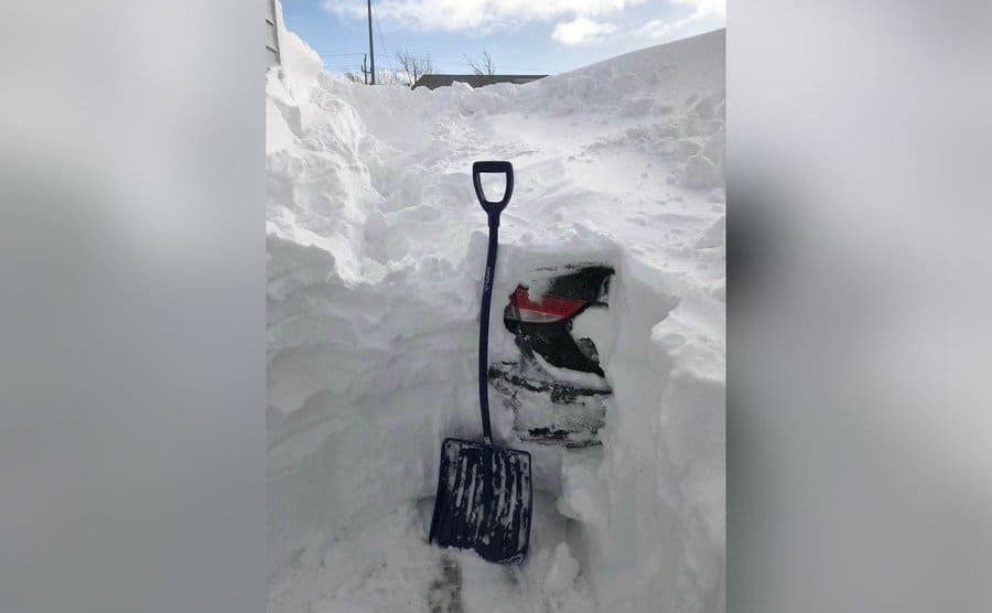 A car hidden under a mountain of snow as someone attempts to dig it out with a shovel.