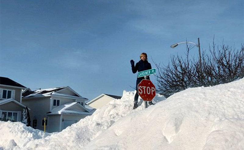 A woman is standing on top of a mountain of snow that has nearly covered a stop sign on a poll.