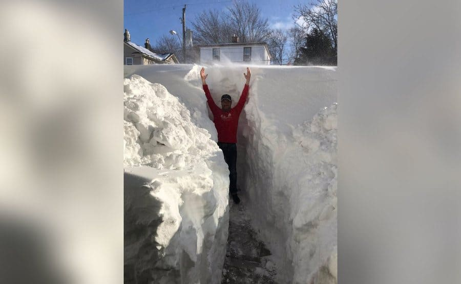 Snow piled up on the road so high that a full-grown man with his arms stretched over his head can barely reach the top.