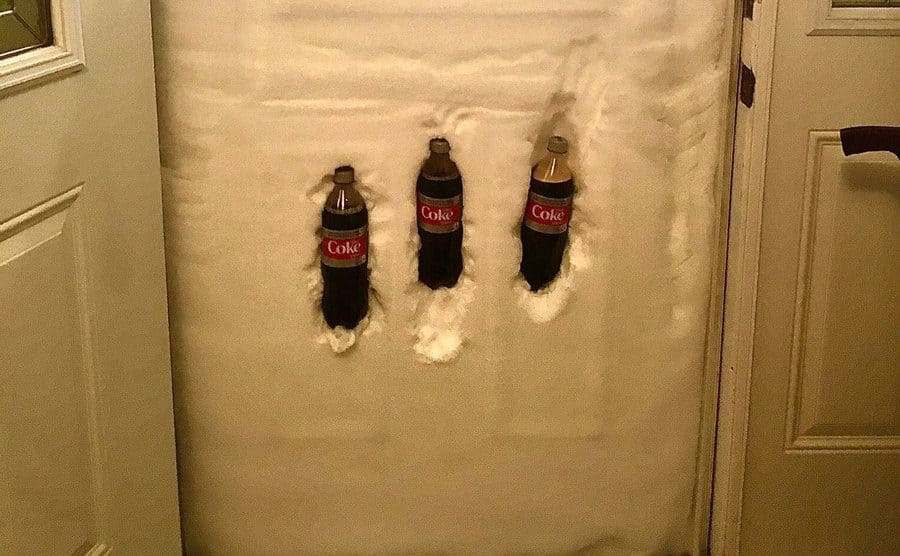 Three Coca Cola bottles placed in the snow that is up against the front door