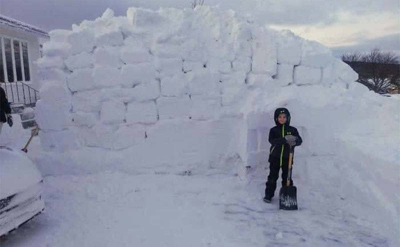 A small child standing next to a snow wall make out of snow bricks.