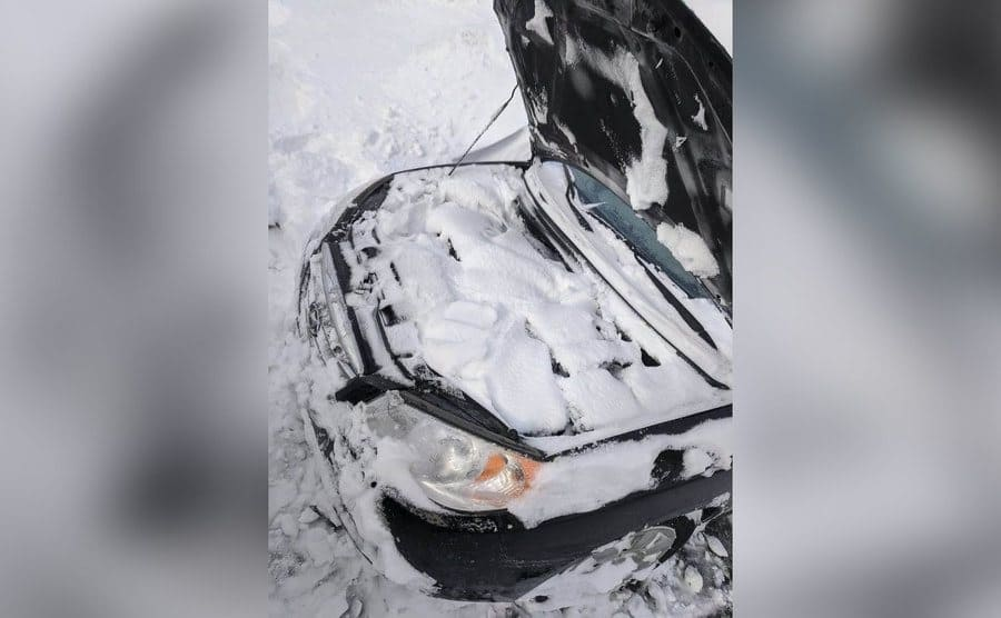 A popped hood of a car revealing the entire engine on the inside is covered in snow.