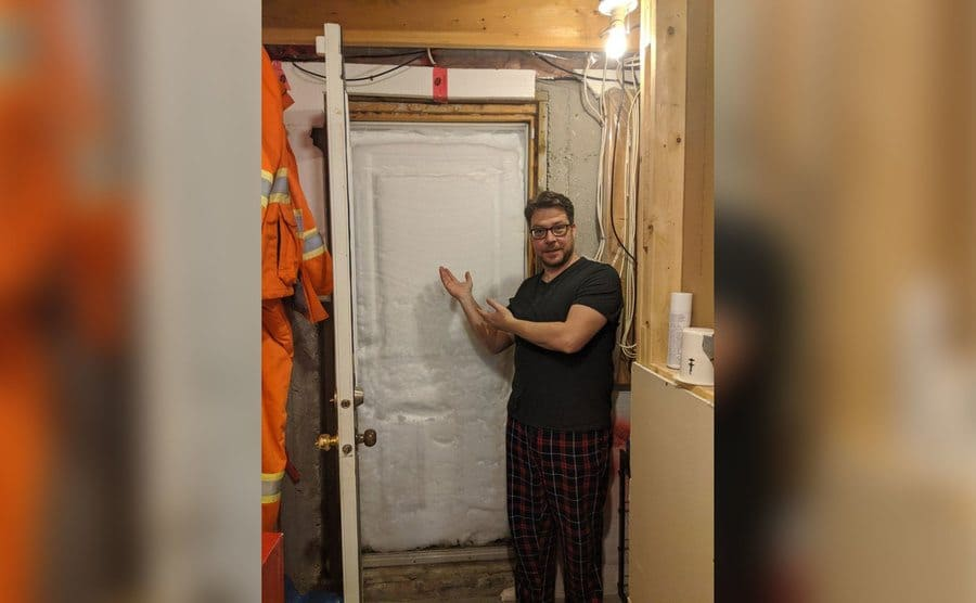A man gesturing at the snow piled up against the front door, no way out.