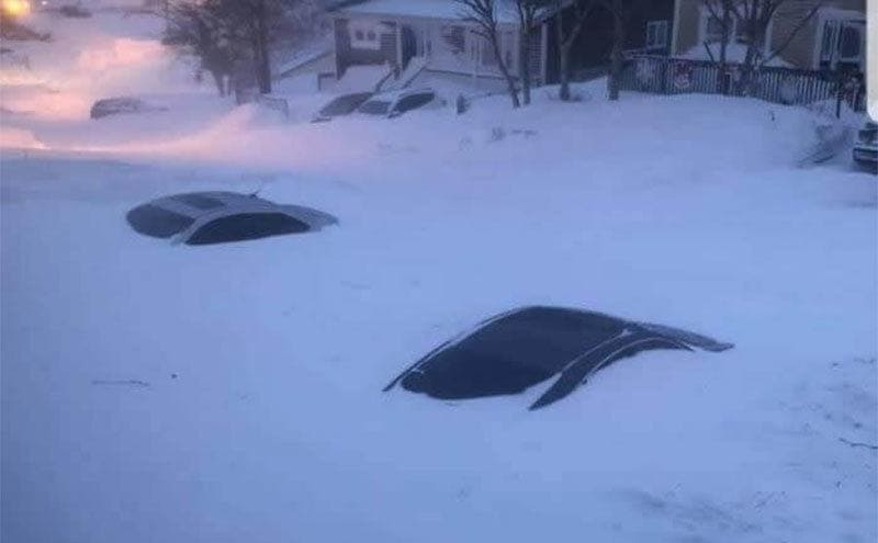 Only the tops of cars are visible on the snow-covered road.