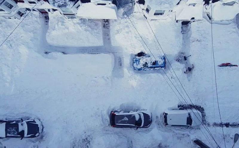 An aerial view of the snow-covered street, the snow has been shoveled away to make what looks like a maze around the cars.