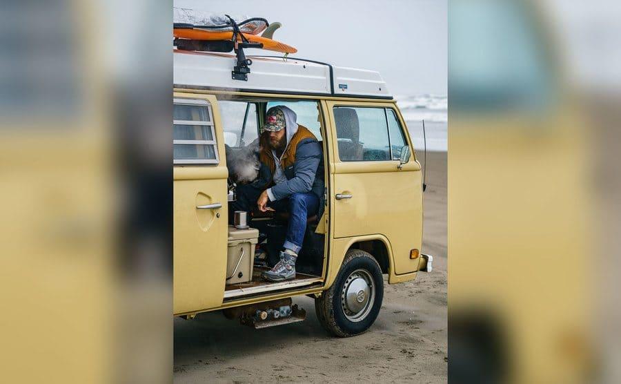 Danuel Having some morning coffee in this parked van.