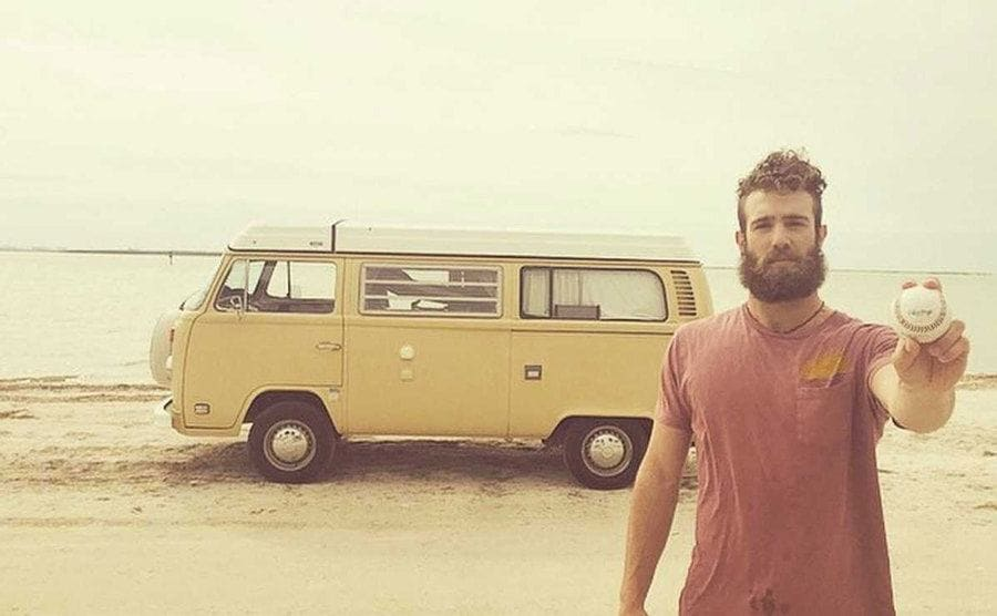 aniel Norris parked his van on the beach and takes a picture while he holds up a baseball.
