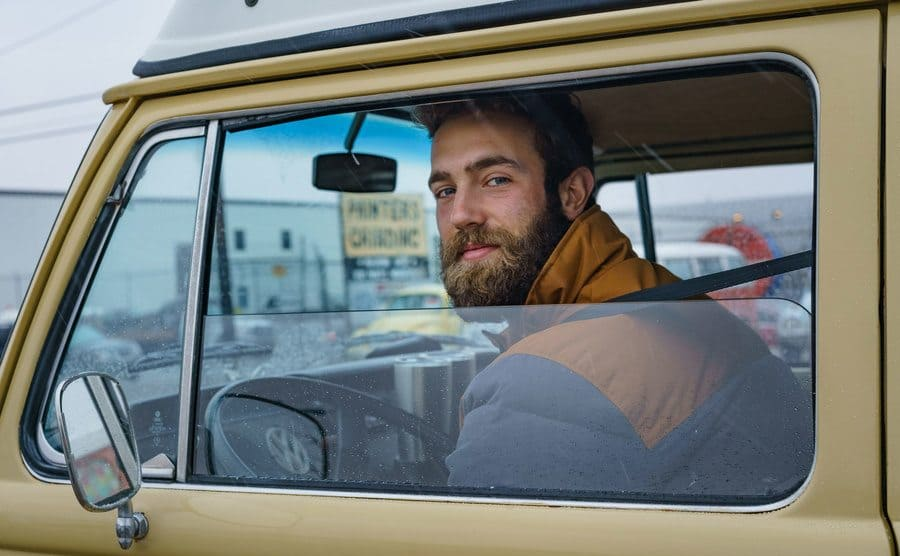aniel Norris looking out the window of the driver seat in his van.