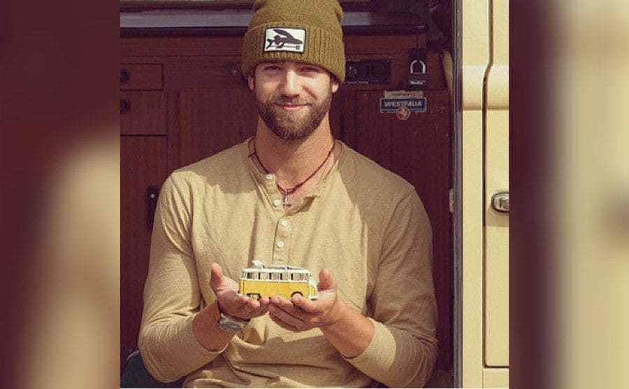 Daniel Norris holding in his hands a mini version of his van.