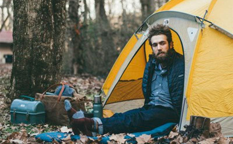 Daniel camping out in the woods.