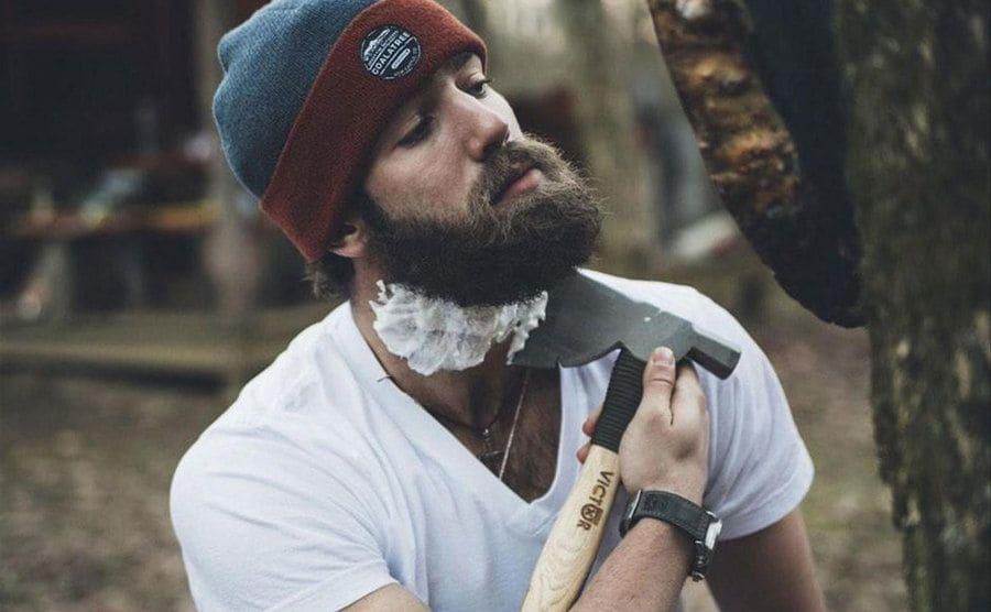 Daniel Norris shaving his beard with an ax.