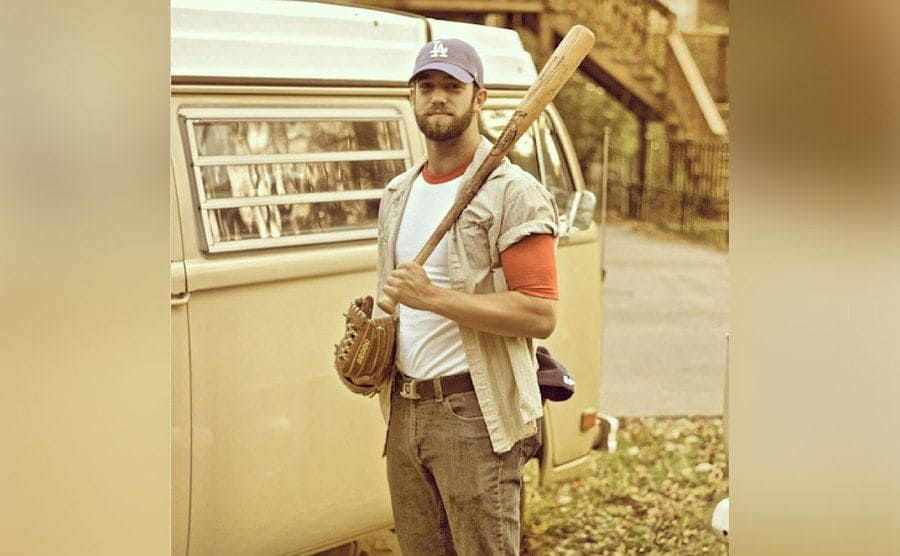 Daniel Norris standing next to his van holding a baseball bat and glove.