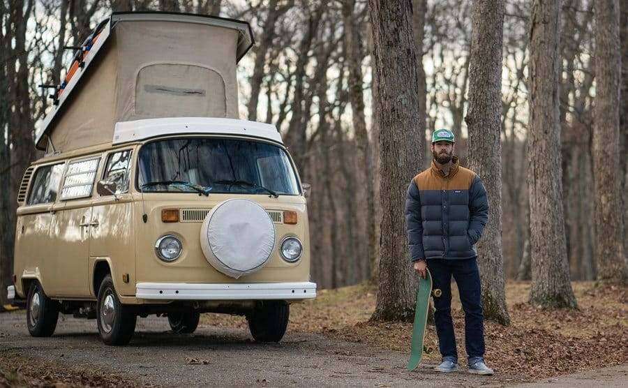 Daniel with his skateboard and his van in the woods.