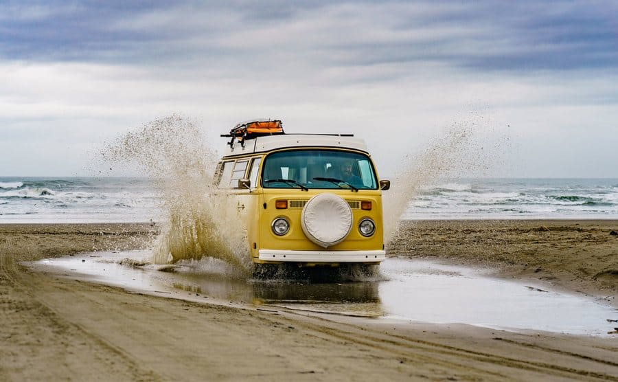 Daniel Norris driving his van through a large puddle on the beach