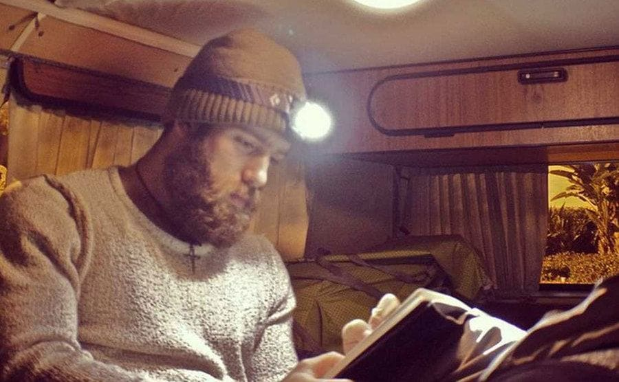 Daniel reading a book in his van to the light of a headlamp.